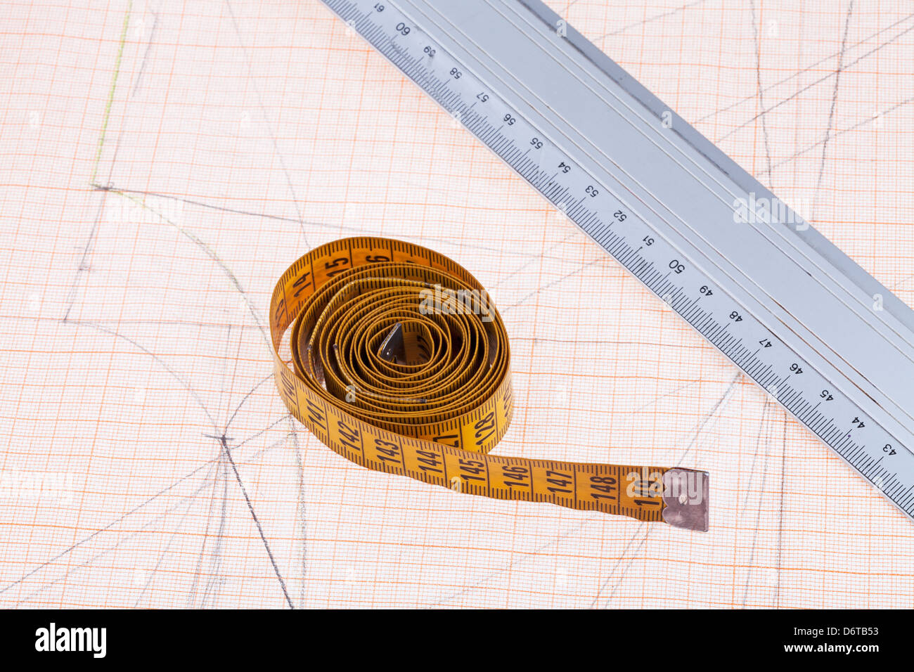 yellow measure tape and metal ruler at graph paper - Stock Image
