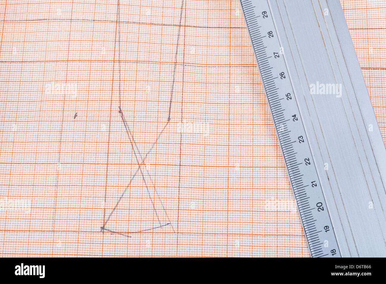 metal ruler at graph paper with dress pattern - Stock Image