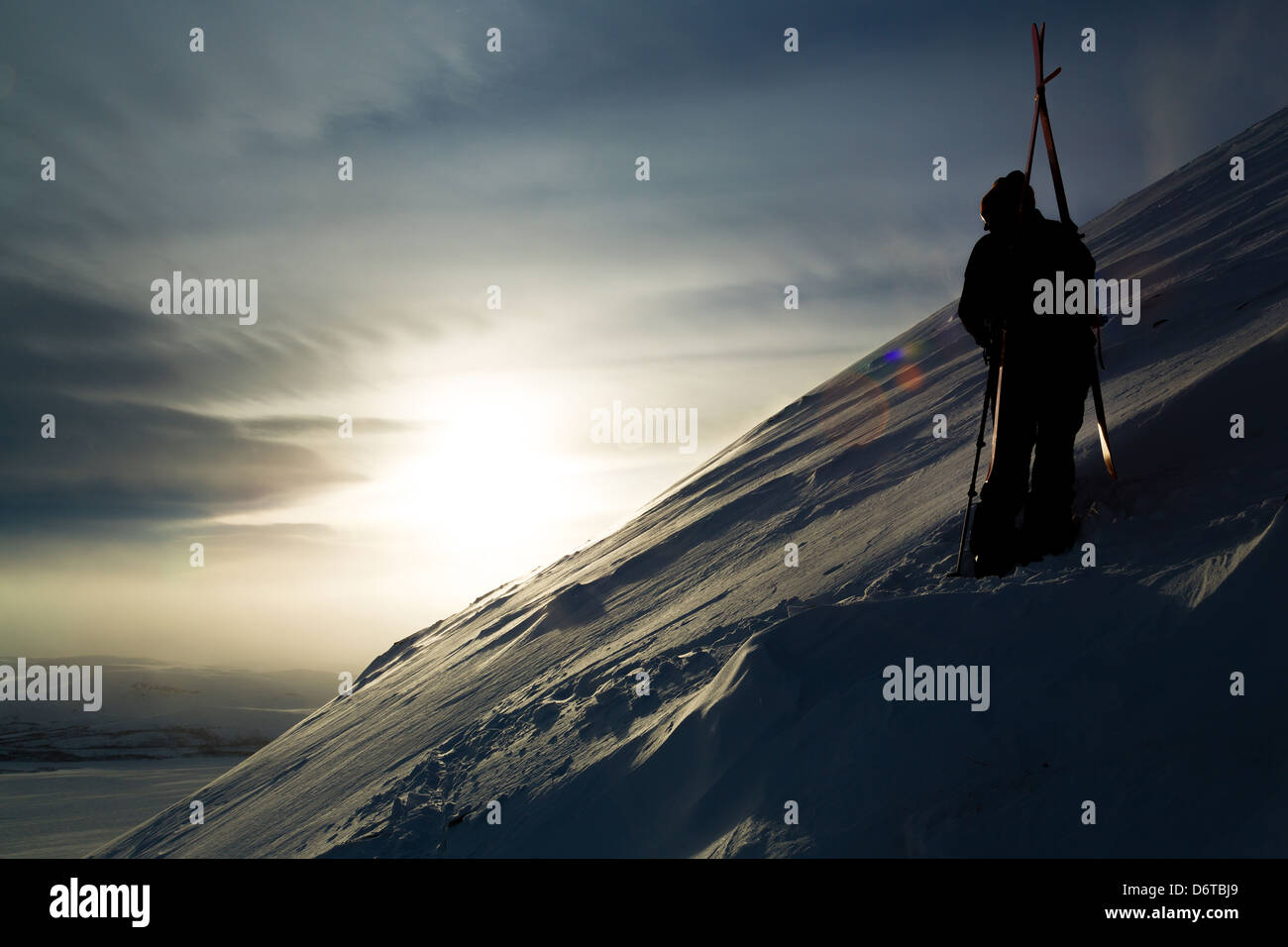 A mountain sun set image, skier or climber looking away from the camera. Dark image with strong contrast. - Stock Image