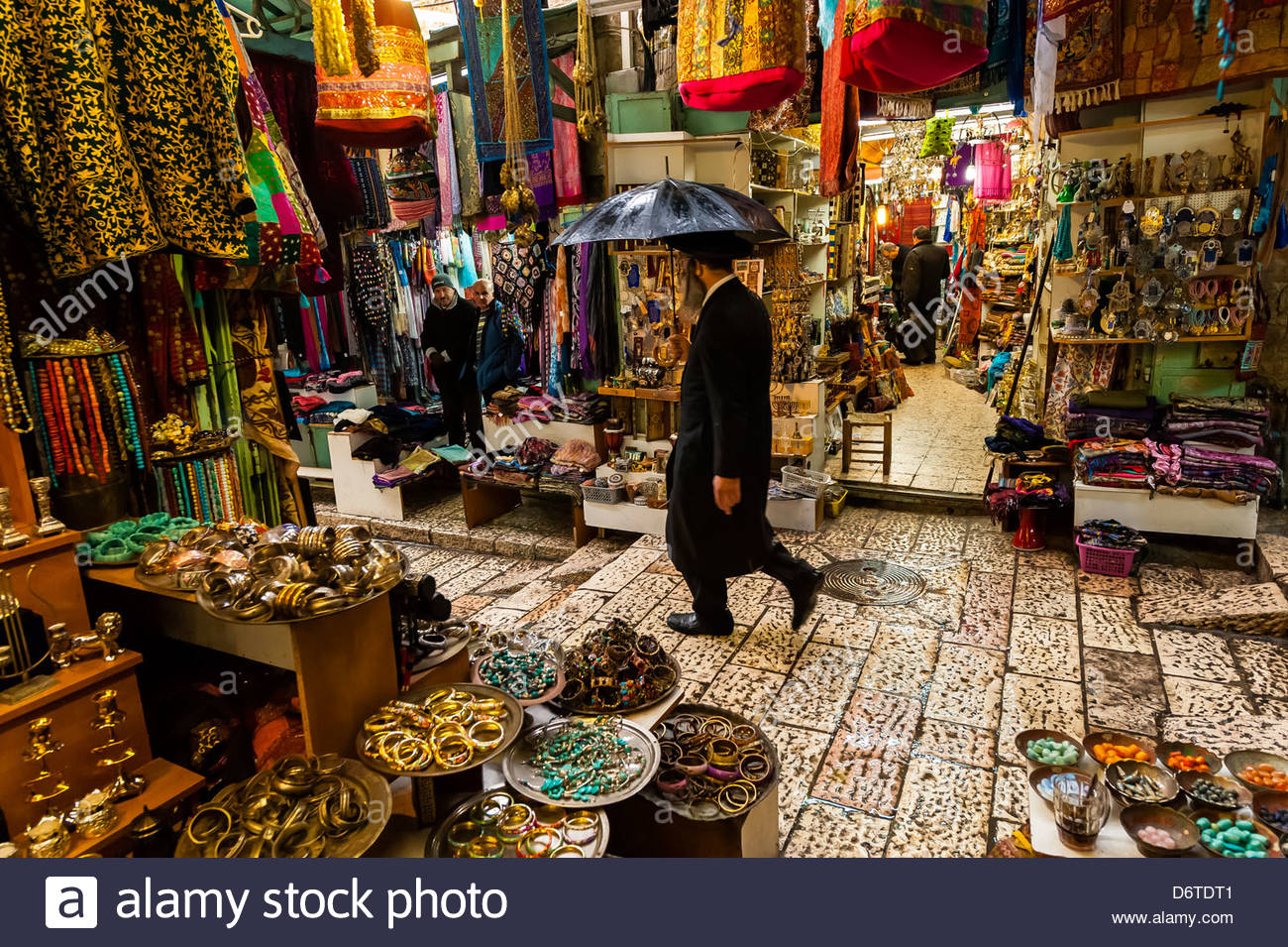 An orthodox Jew walking through the Arab bazaar (suq) in the old city of Jerusalem, Israel in the rain. - Stock Image