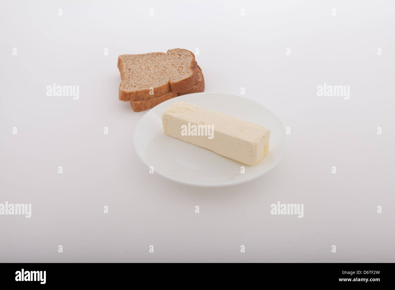 Butter stick on a white  table plate with two slices of wheat bread Stock Photo