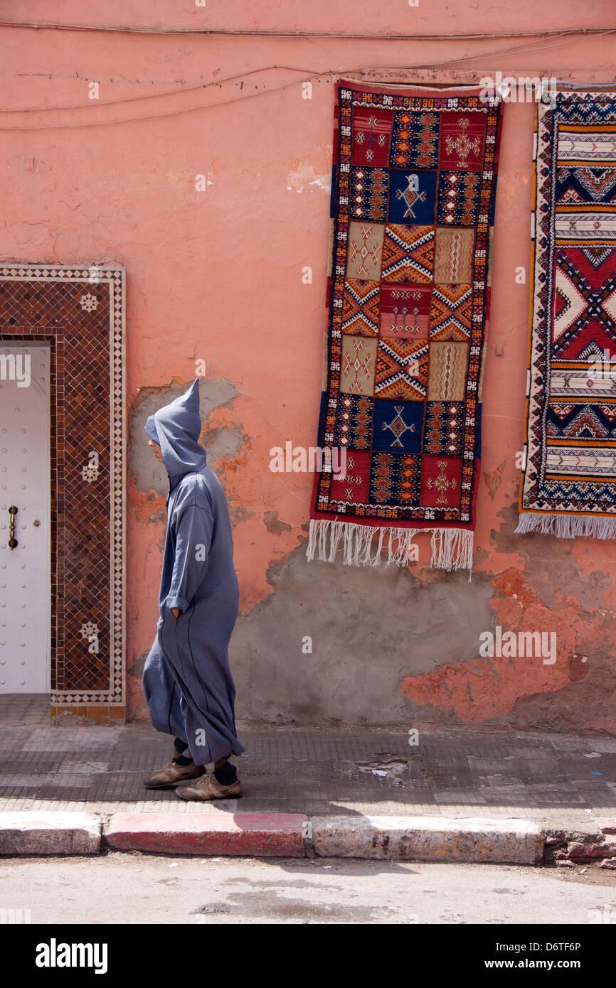 Berber man walking through Marrakech, Morocco, with hanging carpets - Stock Image