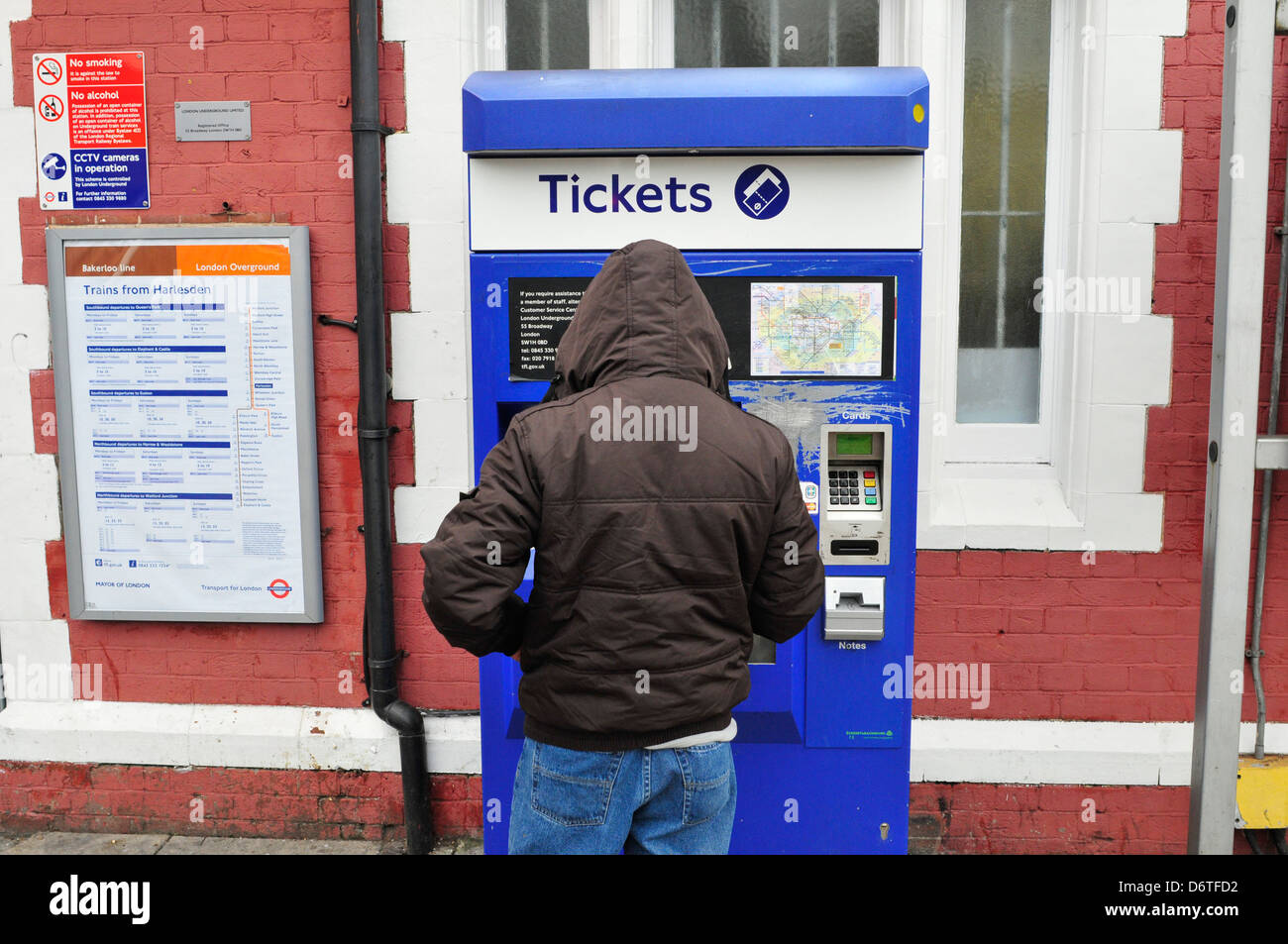 A young man uses a ticket machine at Harlesden station, London, UK - Stock Image