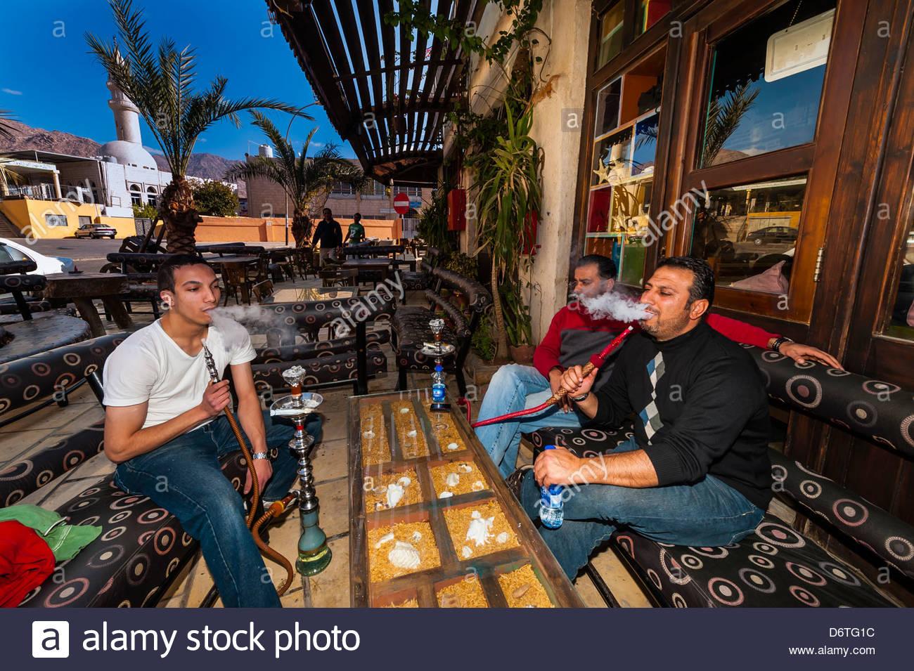 Men smoking sheesha (water pipe) at an outdoor cafe, Aqaba, Jordan - Stock Image