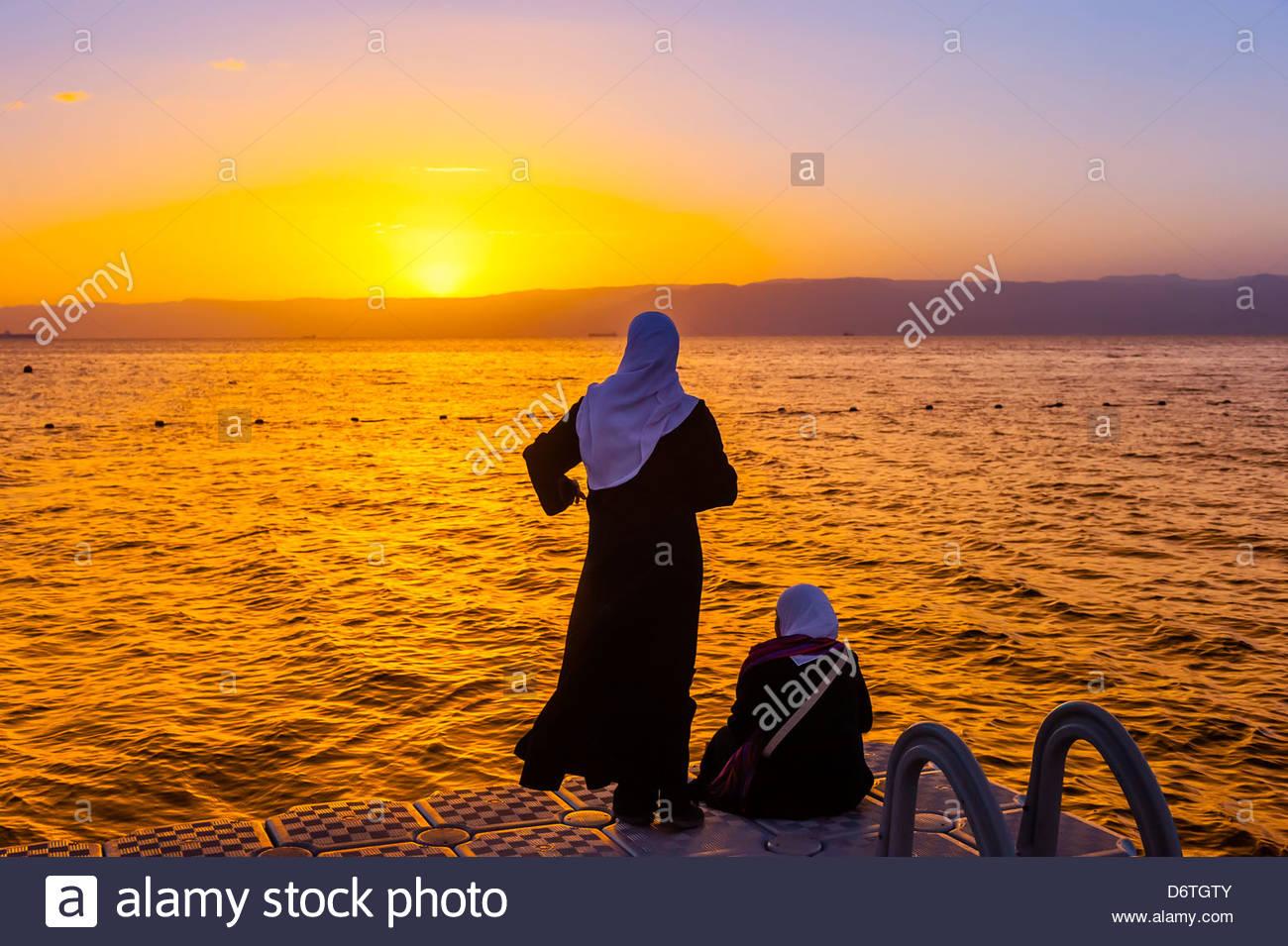 Jordanian women watching the sunset across the Gulf of Aqaba, Red Sea, Jordan from a dock at the Radisson Blu Tala - Stock Image