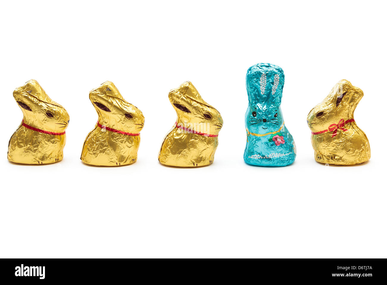 Four yellow gold wrapped chocolate Easter bunnies looking at one blue Easter bunny to illustrate stand out from - Stock Image
