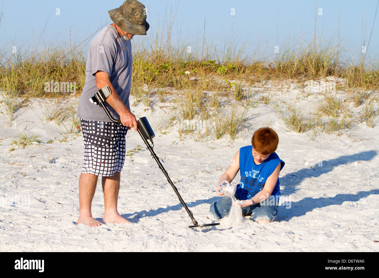 Father and son using a metal detector at the beach on the gulf coast of Florida, USA. - Stock Image