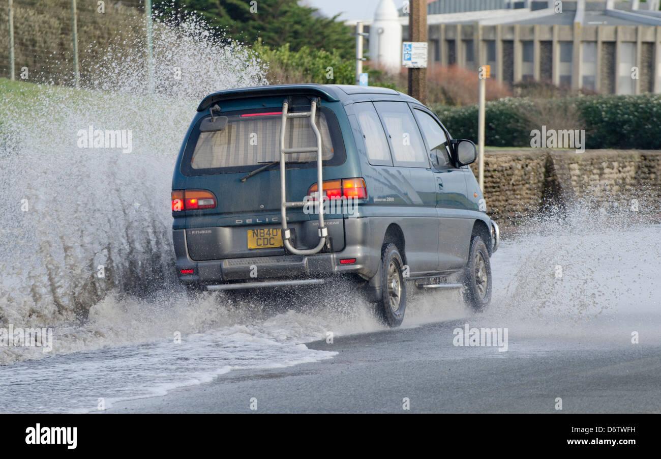 Car driving through deep puddle. - Stock Image