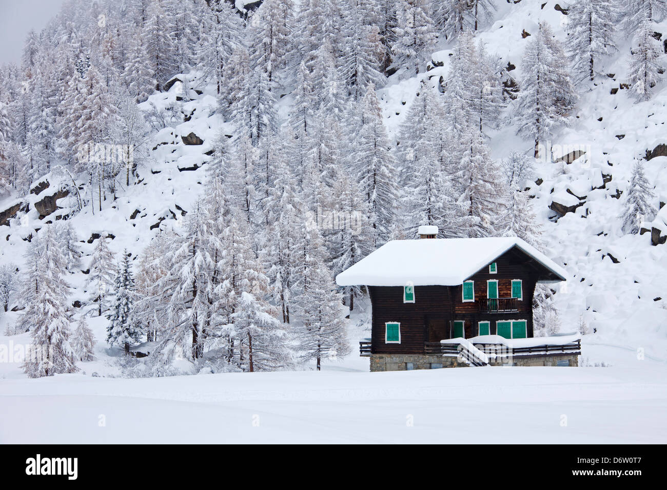 Wooden chalet in the snow in winter in the Gran Paradiso National Park, Valle d'Aosta, Italy - Stock Image