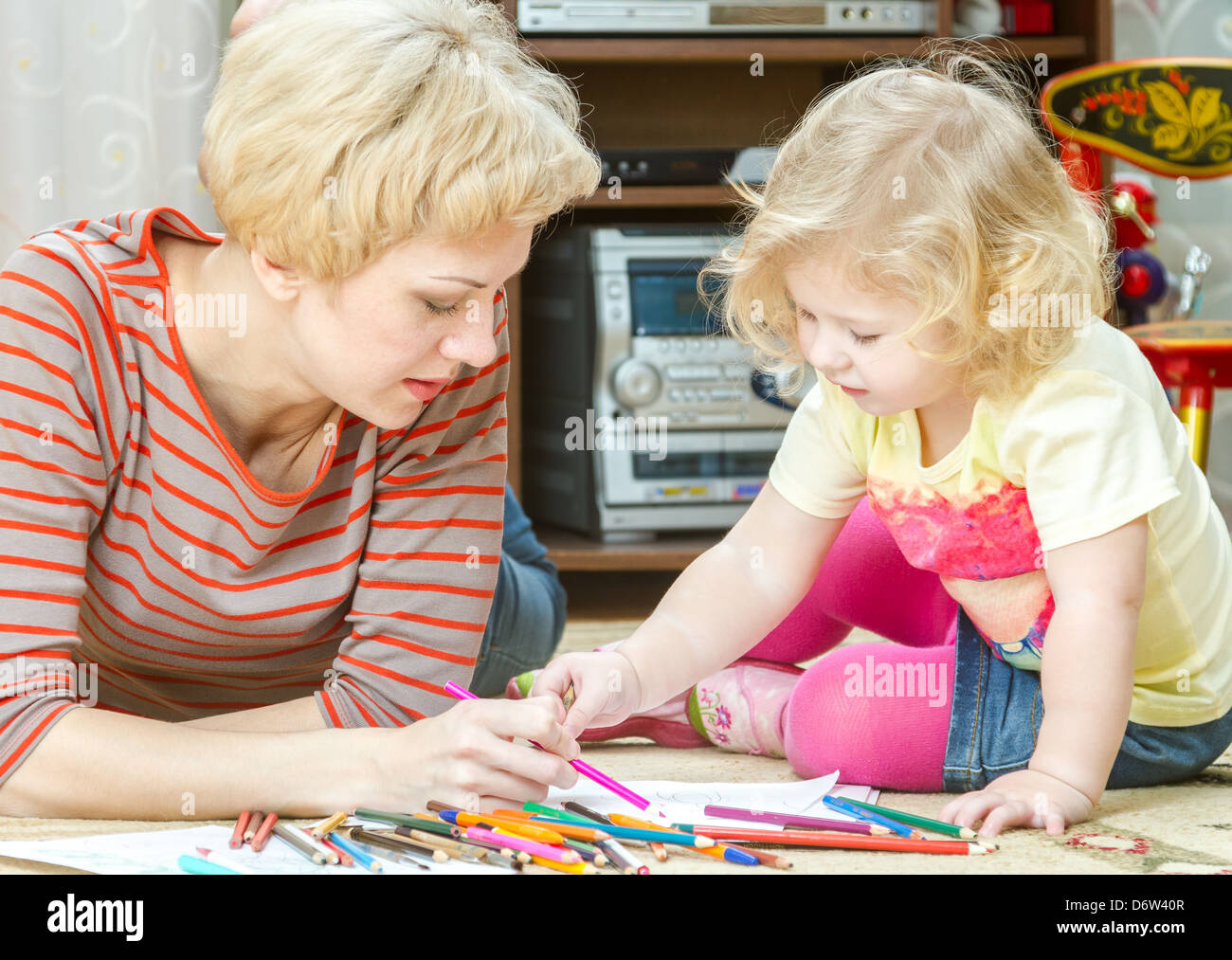 Mother with a little daughter draw pencils - Stock Image