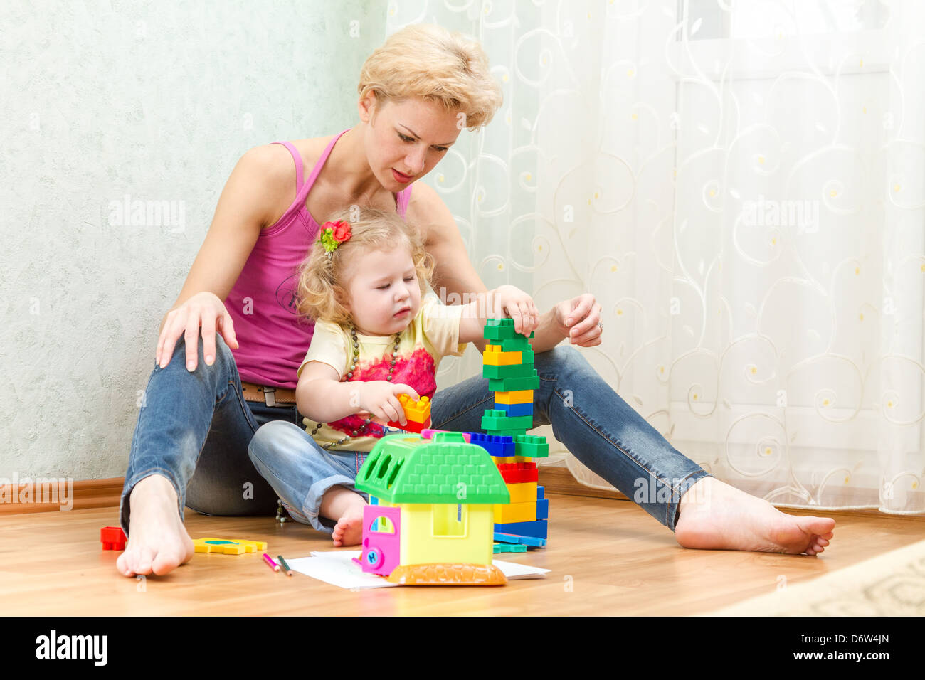 Mother with a little daughter playing with blocks - Stock Image
