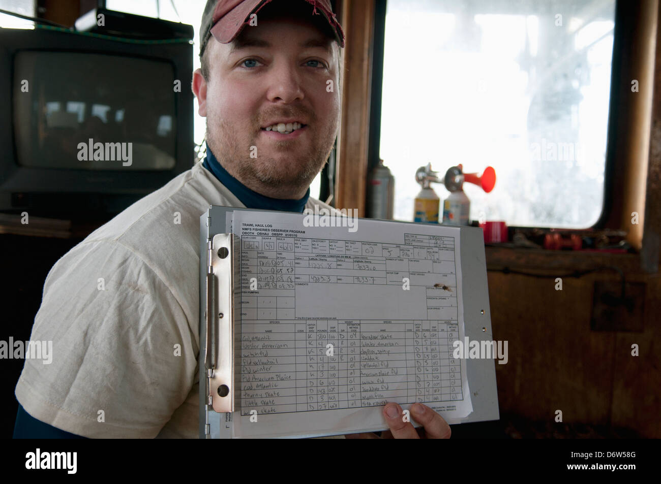 Fisheries Inspector holds chart with catch details. Stellwagen Banks, New England, United States, North Atlantic - Stock Image