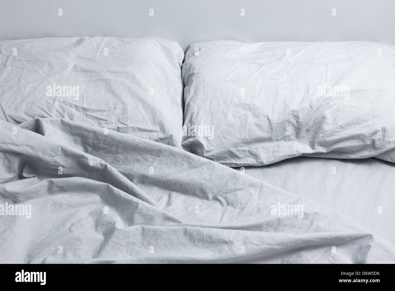Messy bed with two pillows, gray bed linen. - Stock Image