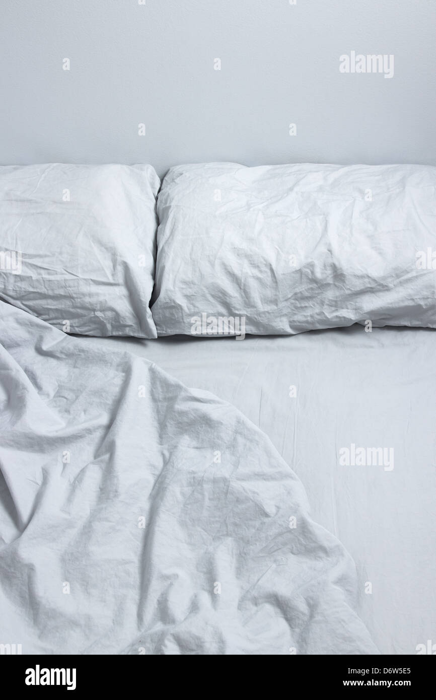 Messy bed with two pillows and gray bedclothes. - Stock Image