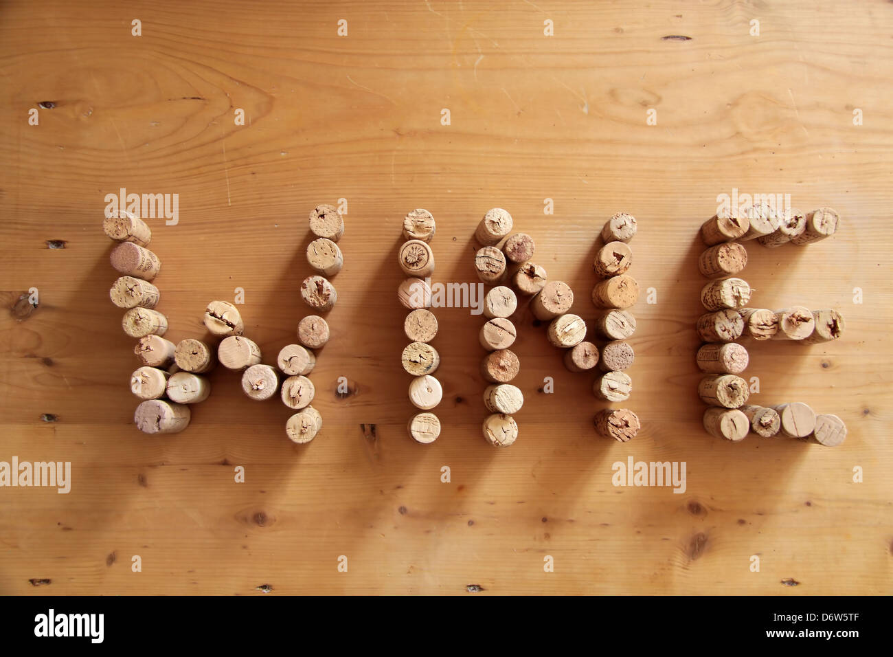 Corks forming the word wine on wooden desk - Stock Image