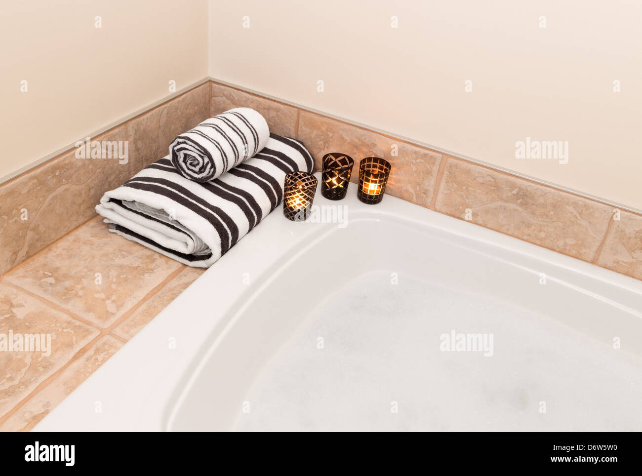 Bath with foam, fresh folded towels and candle lights Stock Photo ...