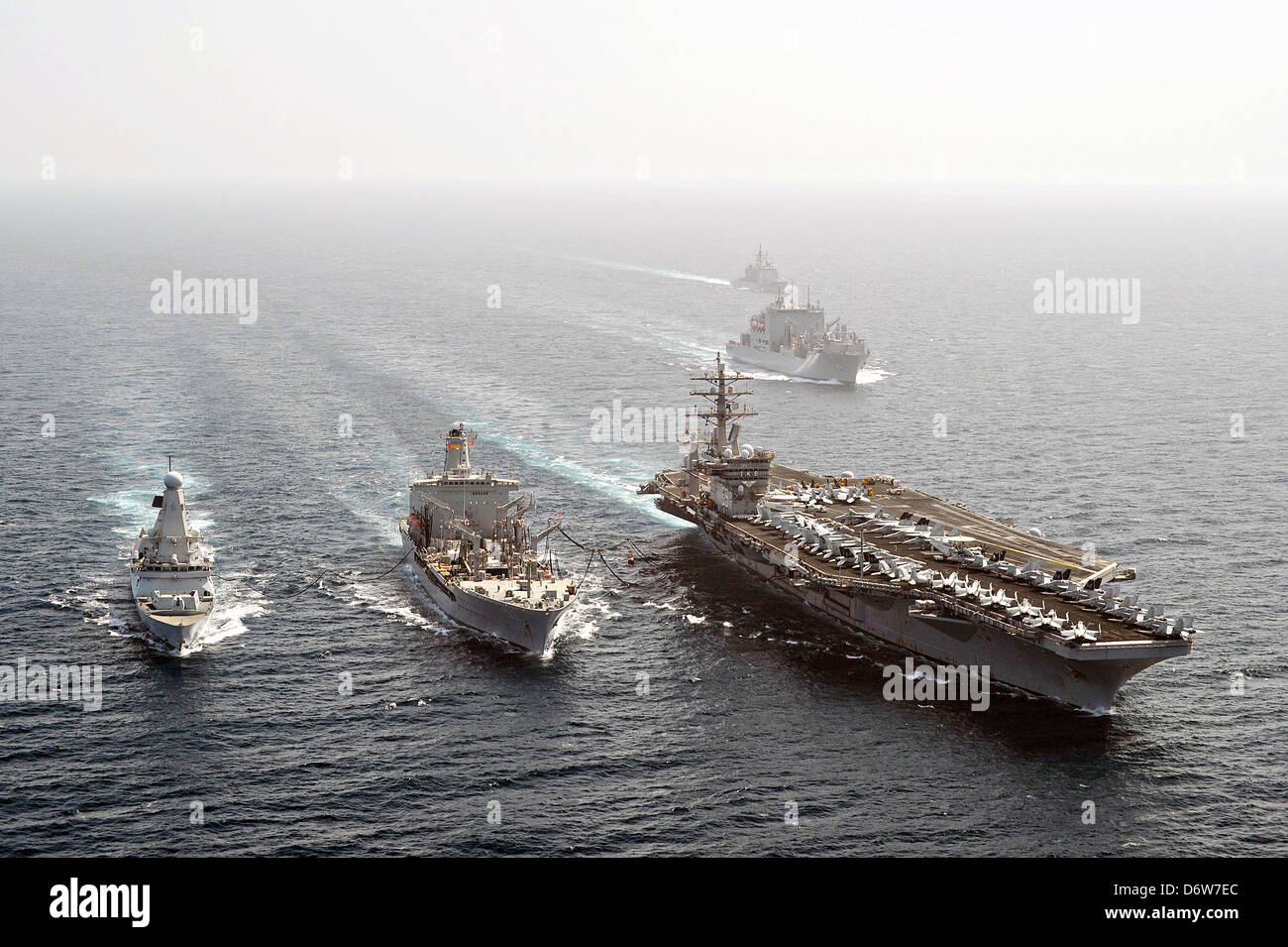 The British destroyer HMS Dragon and the US Navy aircraft carrier USS Dwight D. Eisenhower steam alongside the fleet - Stock Image