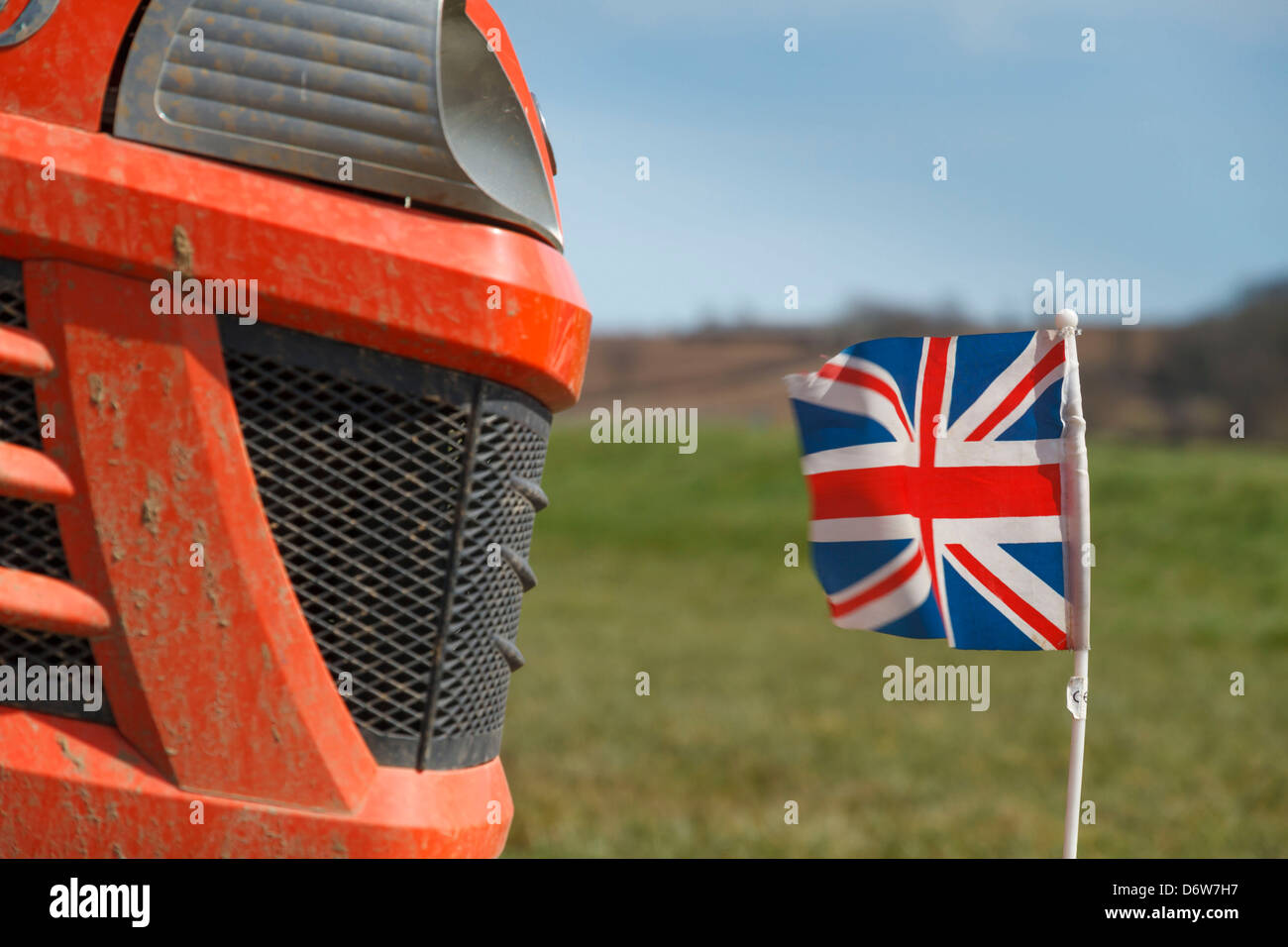 A union jack British flag on the front of a small red tractor lawnmower lawn mower Stock Photo