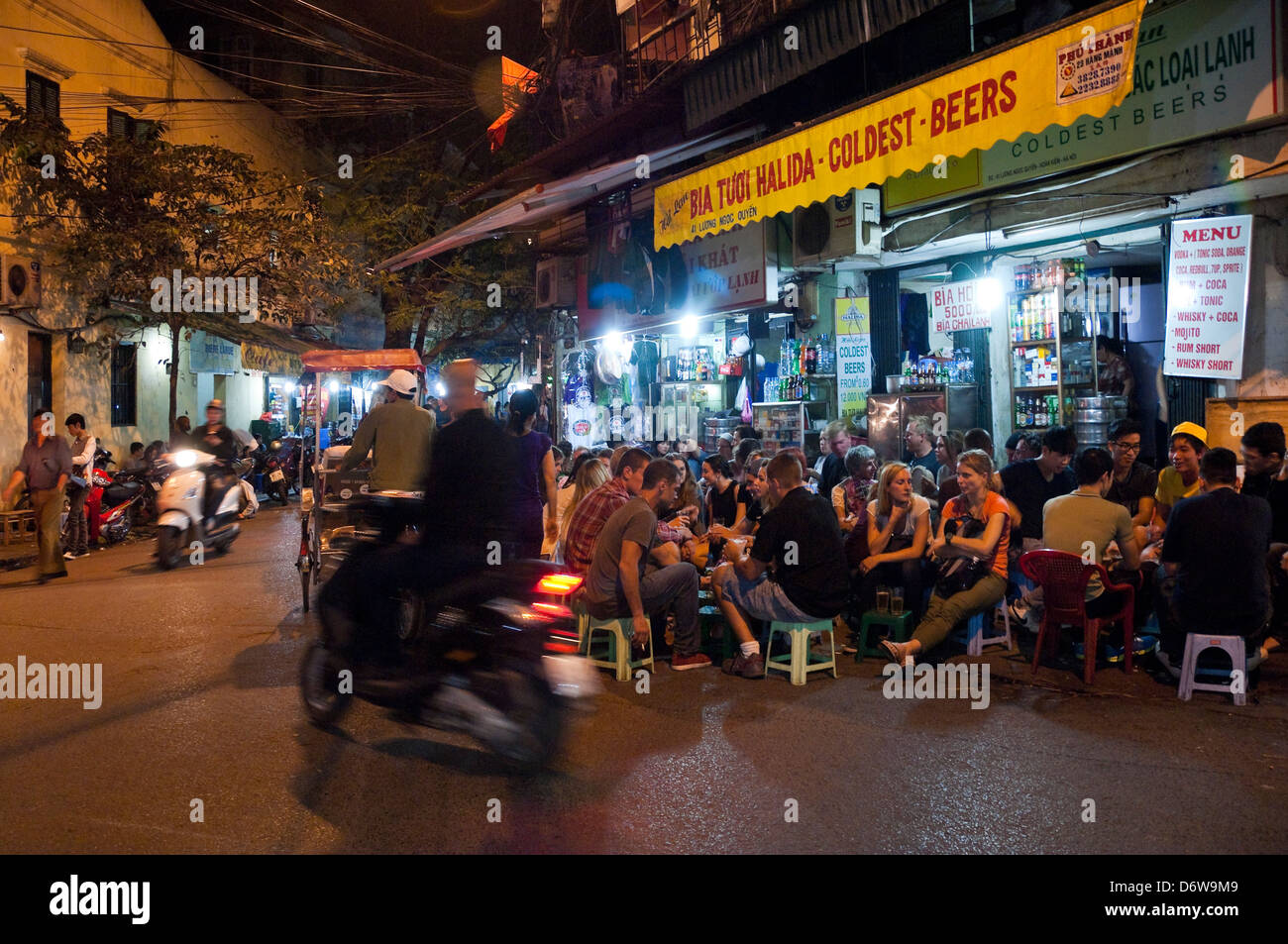 Horizontal wide angle of lots of tourists and locals drinking beer on the street in the Old Quarter in Hanoi at Stock Photo