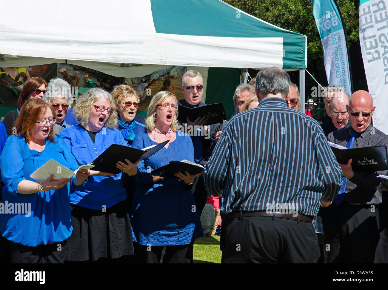 A choir in full voice at an outside venue - Stock Image