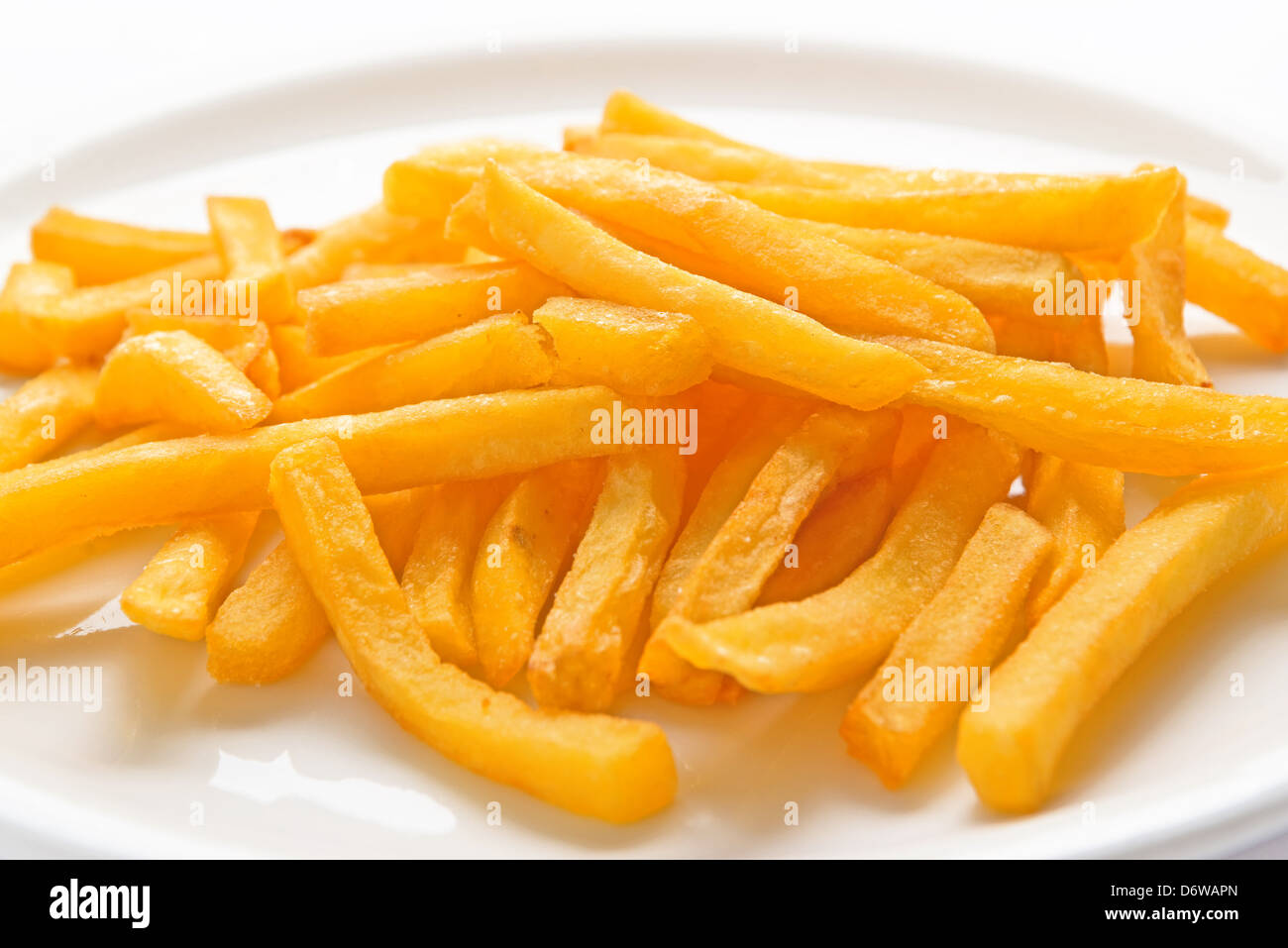French fries served on white flat plate. - Stock Image