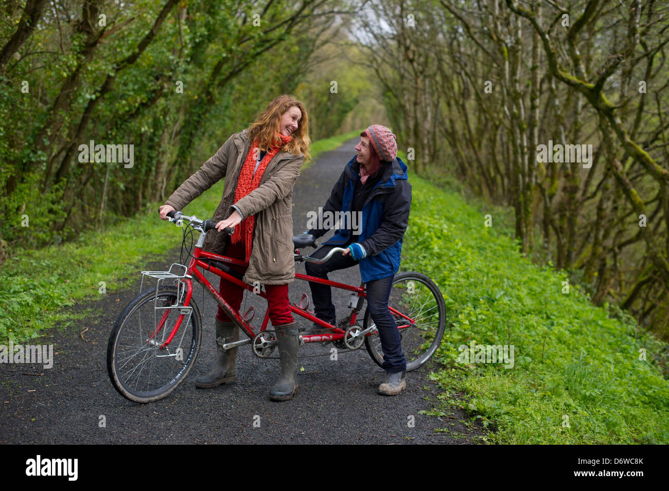 Two ladies on a tandem bicycle on part of the Tarka Trail, a cycle path in North Devon. - Stock Image