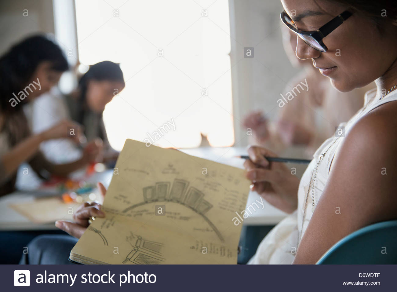 Young woman holding sketch book with colleagues working in background - Stock Image