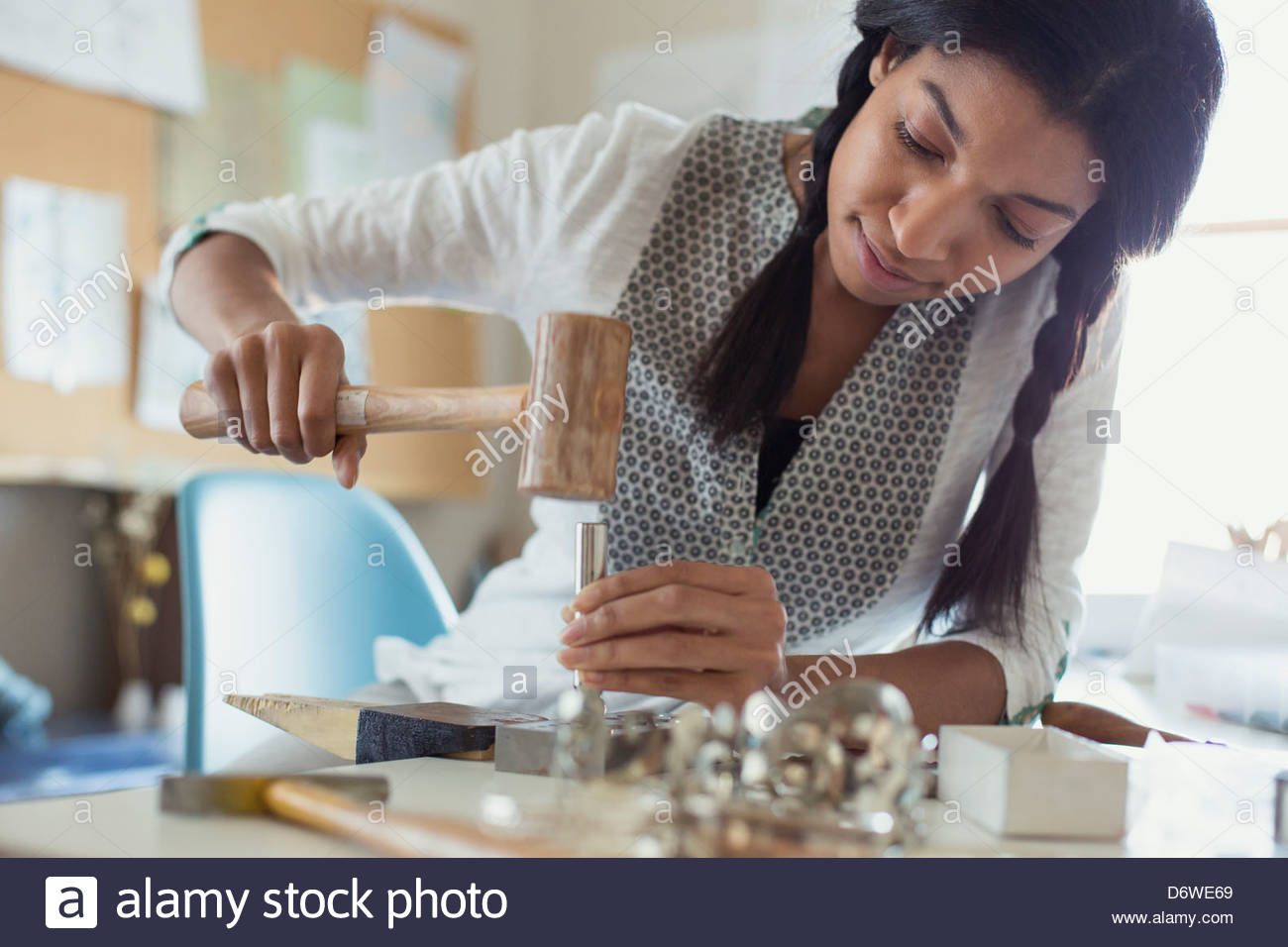 Mid adult female artist making jewelry at desk - Stock Image