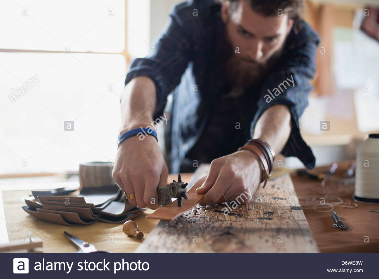 Man punching holes in leather belt at table - Stock Image