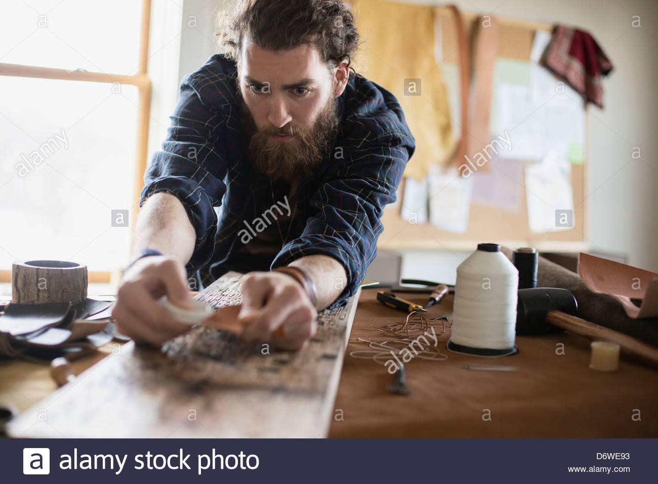 Young man finishing leather belt at workshop - Stock Image