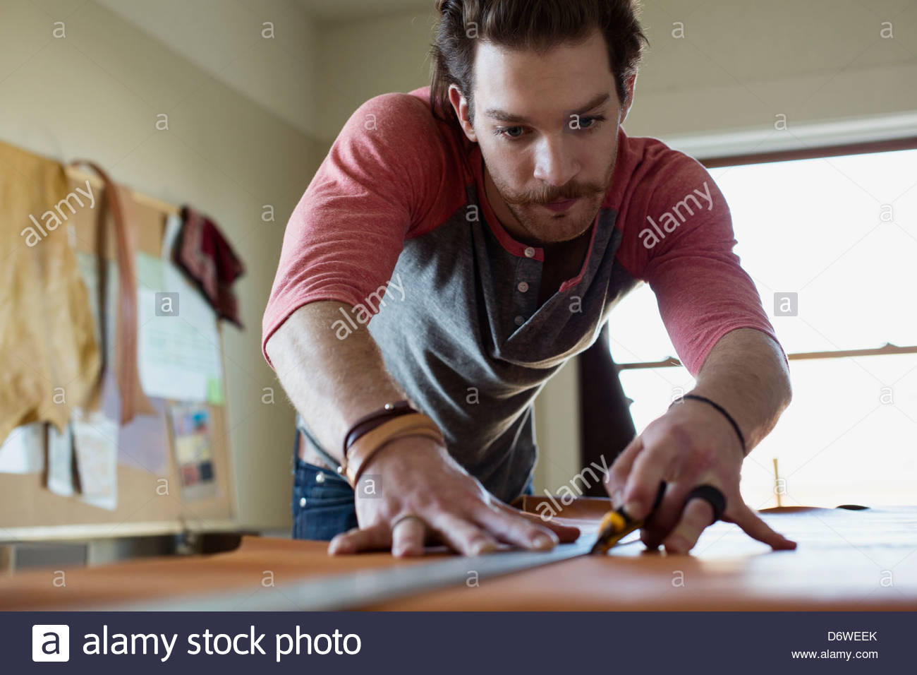 Young man measuring and cutting leather in workshop Stock Photo