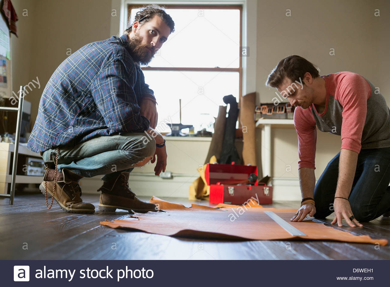 Portrait of young man crouching while colleague examines leather in workshop - Stock Image