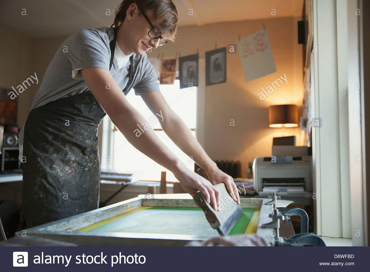 Male design professional working on silk screen - Stock Image