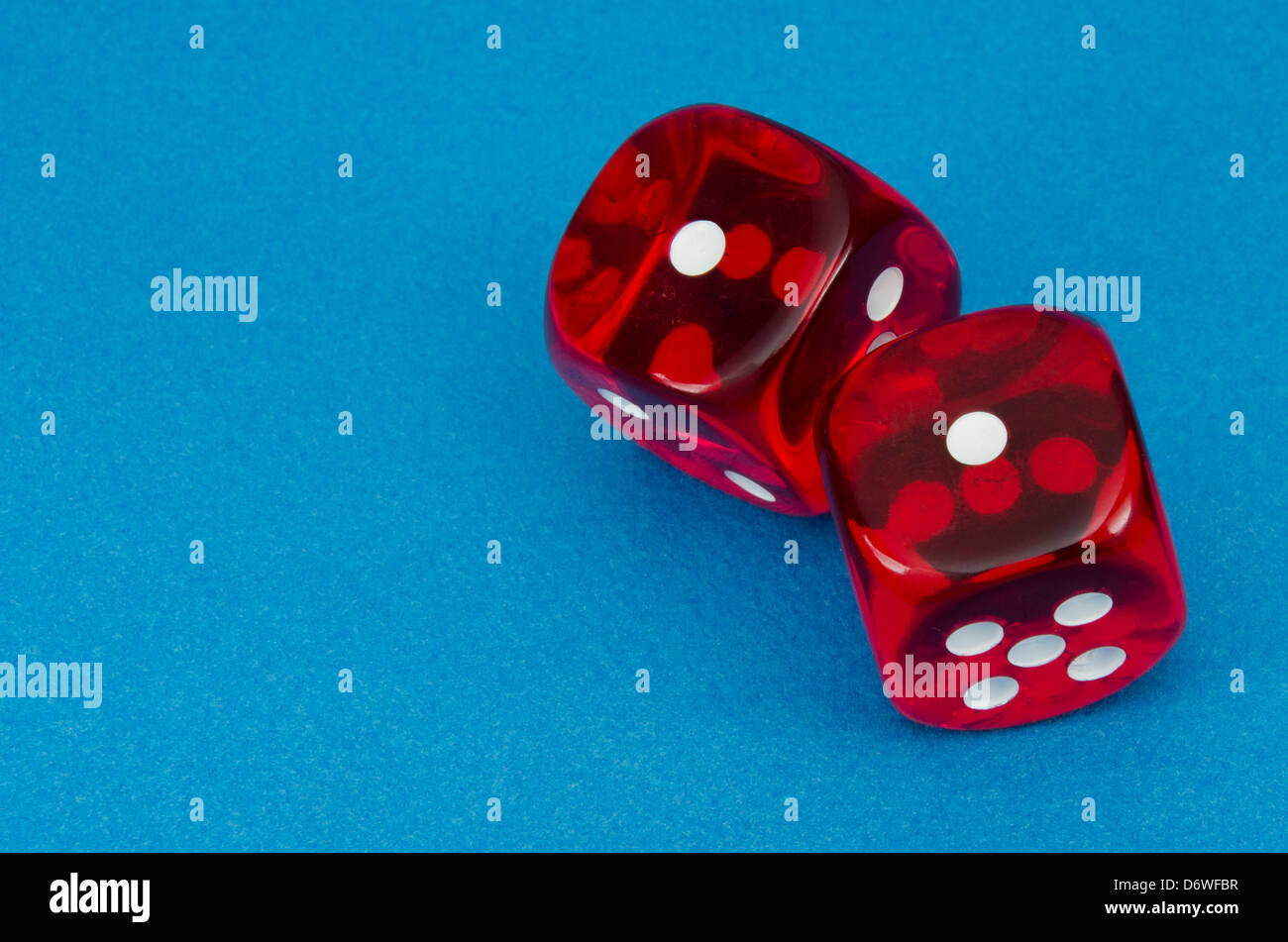 Pair of red dice over blue bakground showing two ones, snake eyes - Stock Image