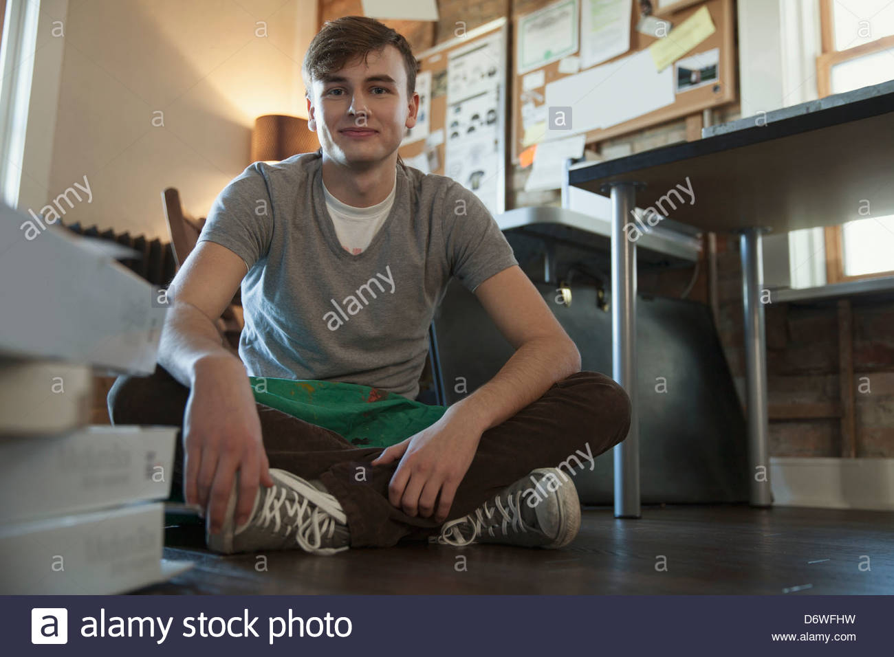 Portrait of young male design professional sitting on floor at workshop - Stock Image
