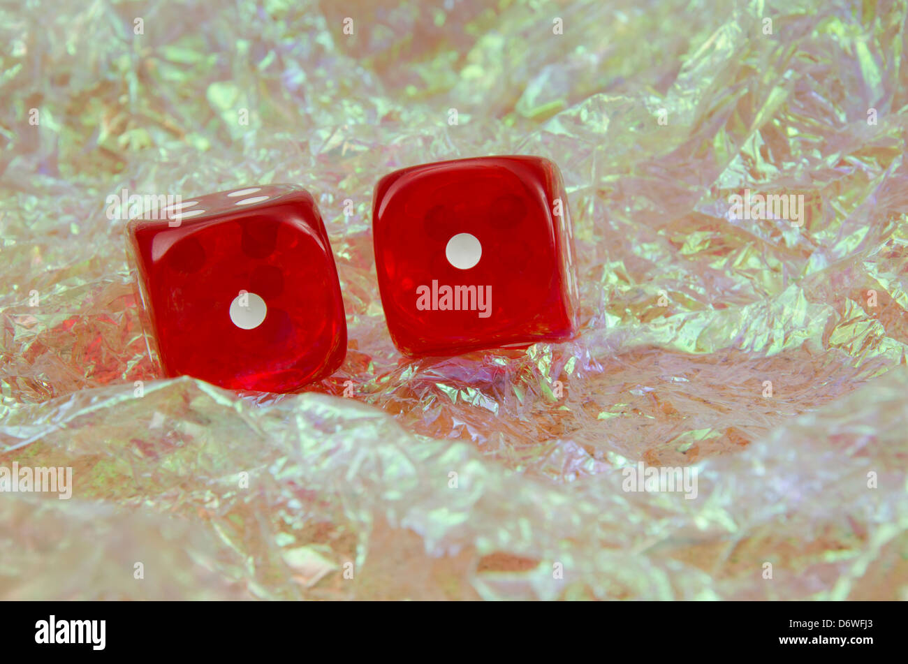 Pair of red dice over a bright, pearly bakground showing two ones, snake eyes - Stock Image
