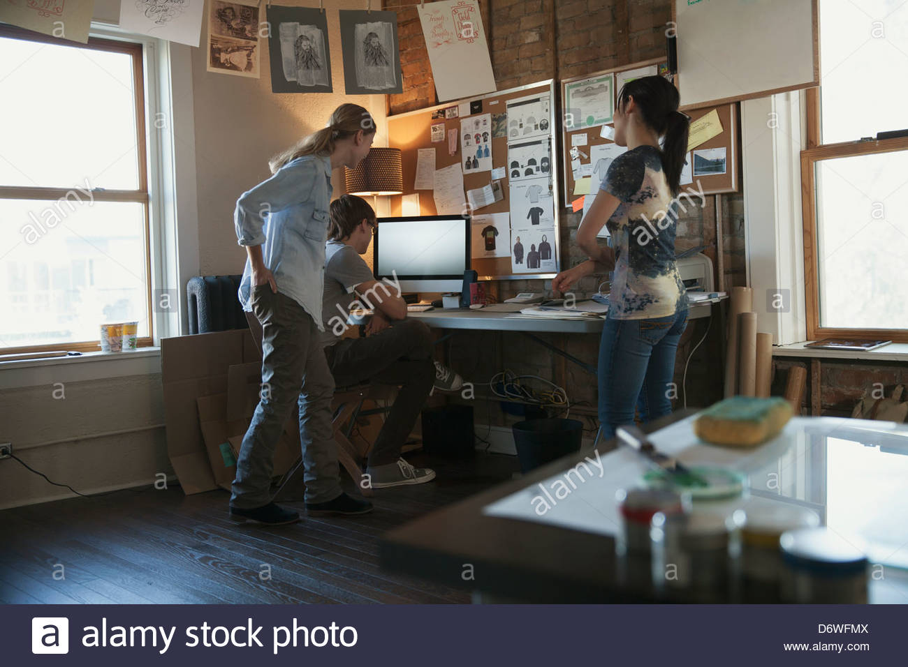 Design professionals working at desktop computer together - Stock Image