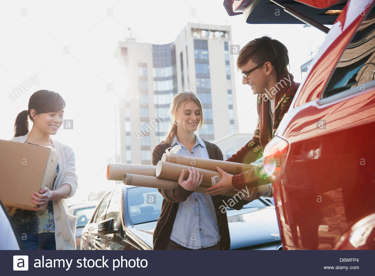 Happy design professionals with packages loading car - Stock Image