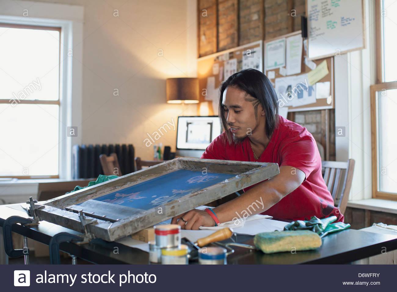 Man using silk screen for T-shirt printing at workshop - Stock Image