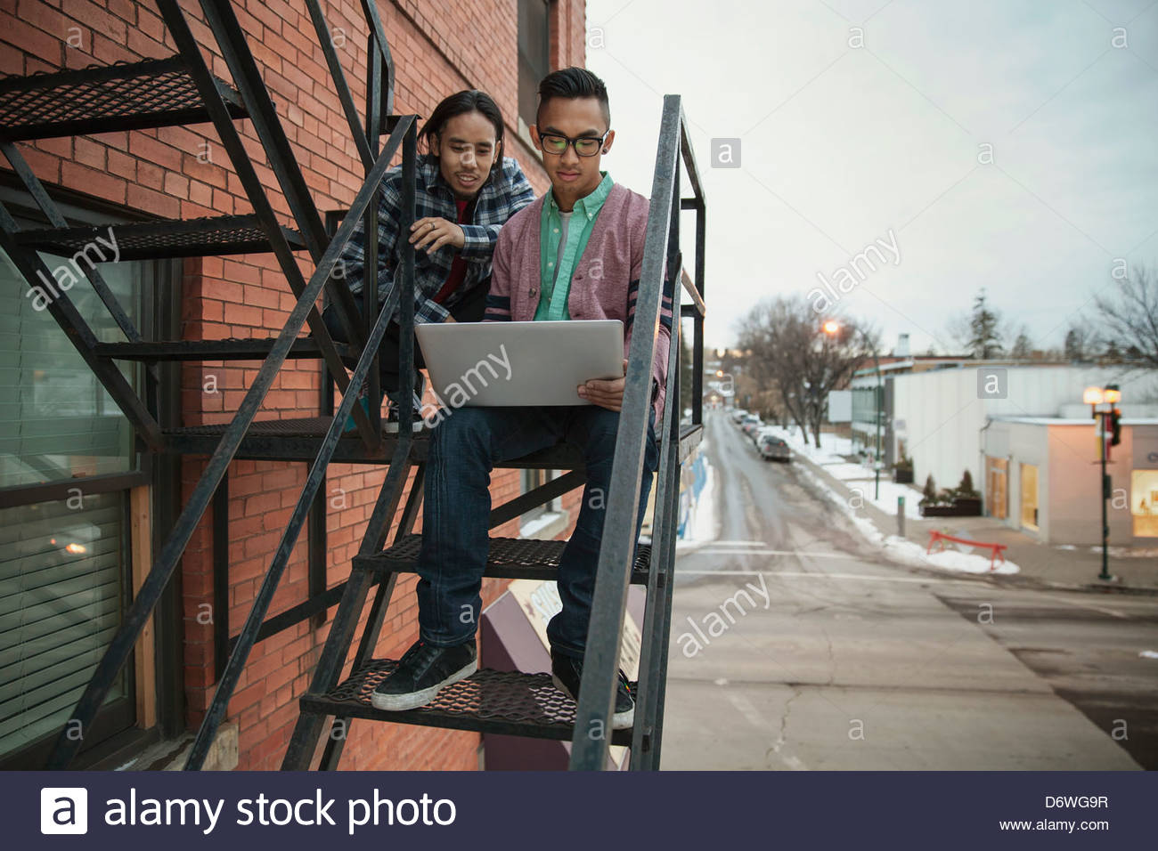 Young male friends using laptop on fire exit staircase - Stock Image