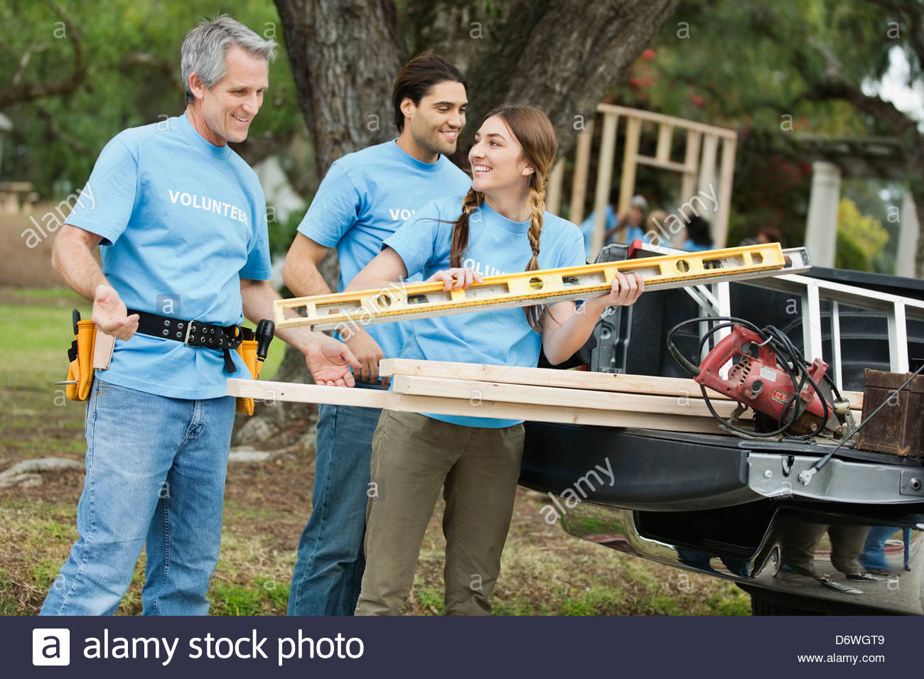 Three volunteers unloading work tools from vehicle in park - Stock Image