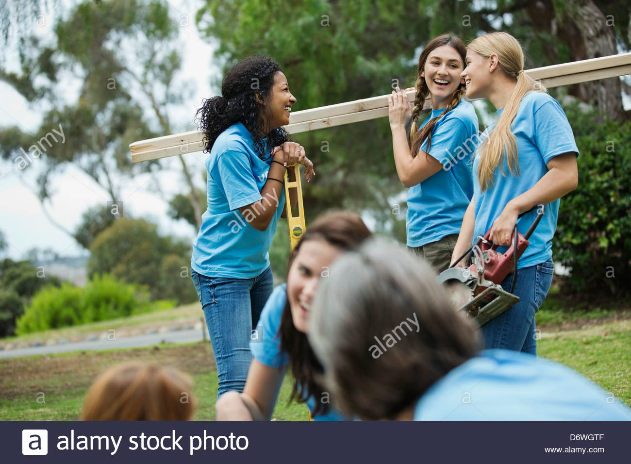 Happy female volunteers working together on construction site - Stock Image
