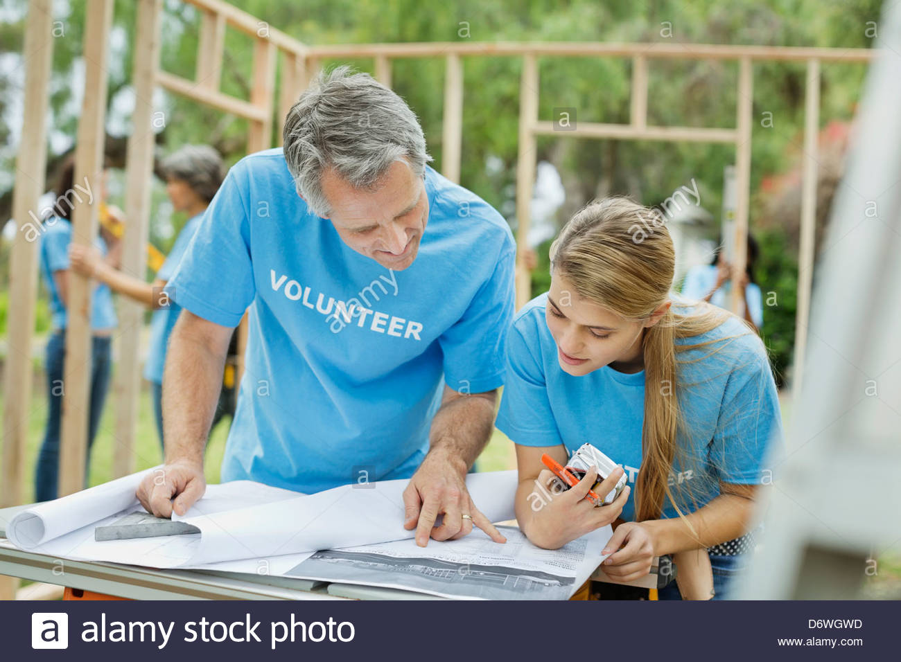 Two volunteers discussing blueprint while people work in background - Stock Image