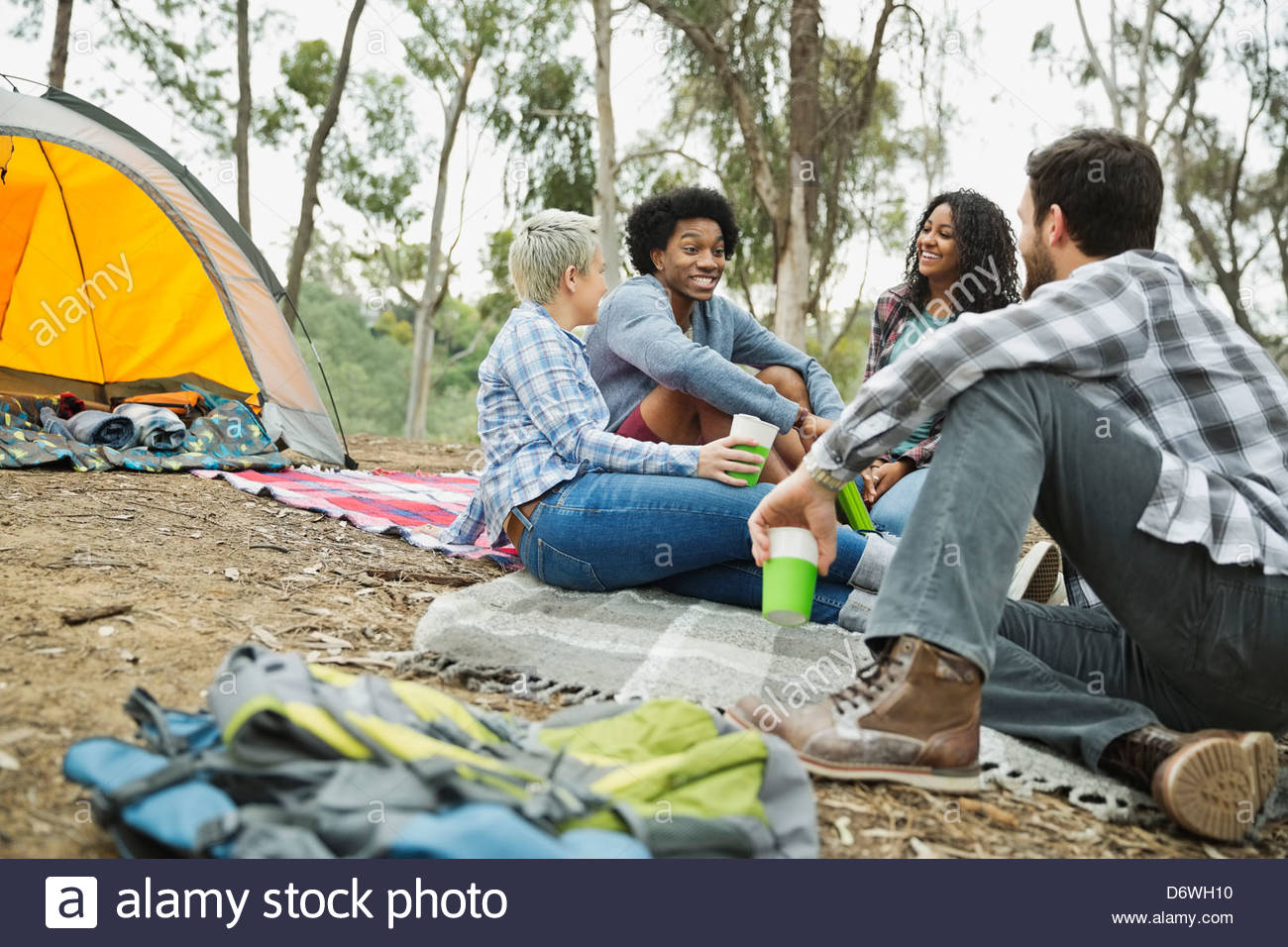 Friends talking while camping outdoors Stock Photo