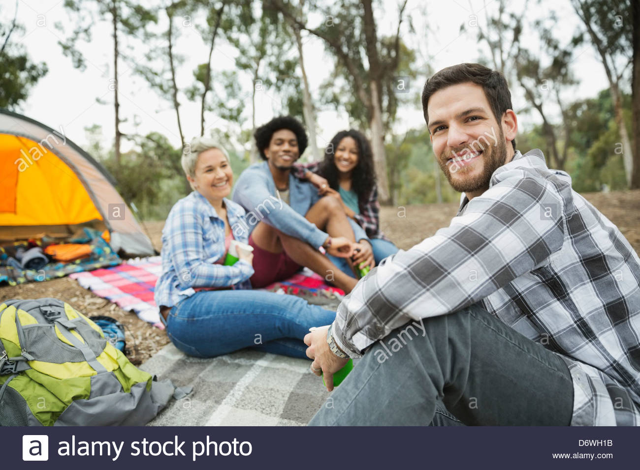 Portrait of mid adult man sitting with friends while camping - Stock Image