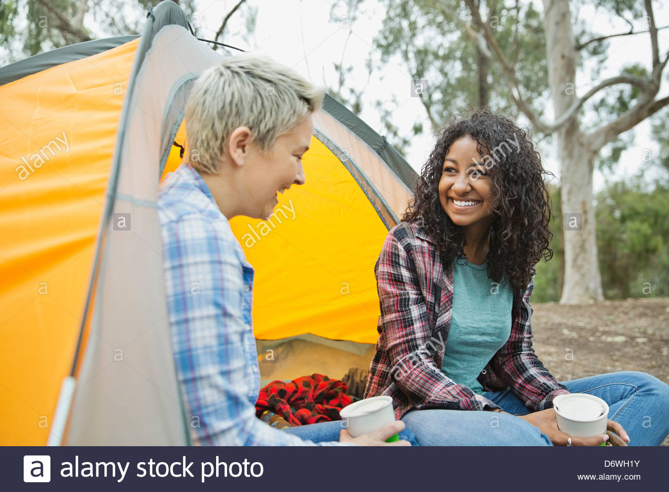 Happy female friends having a conversation while camping - Stock Image