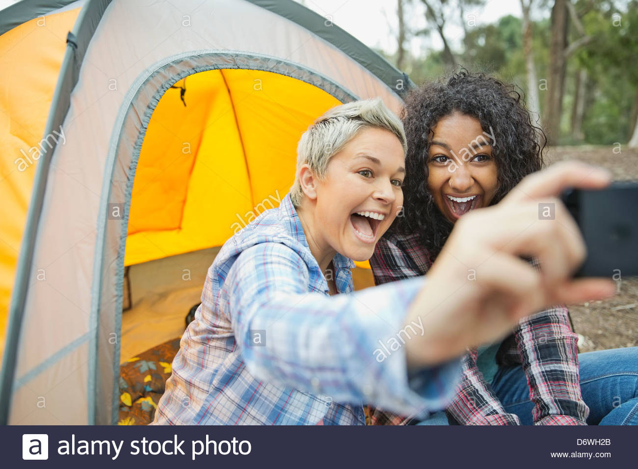 Happy female friends taking self portrait while camping - Stock Image