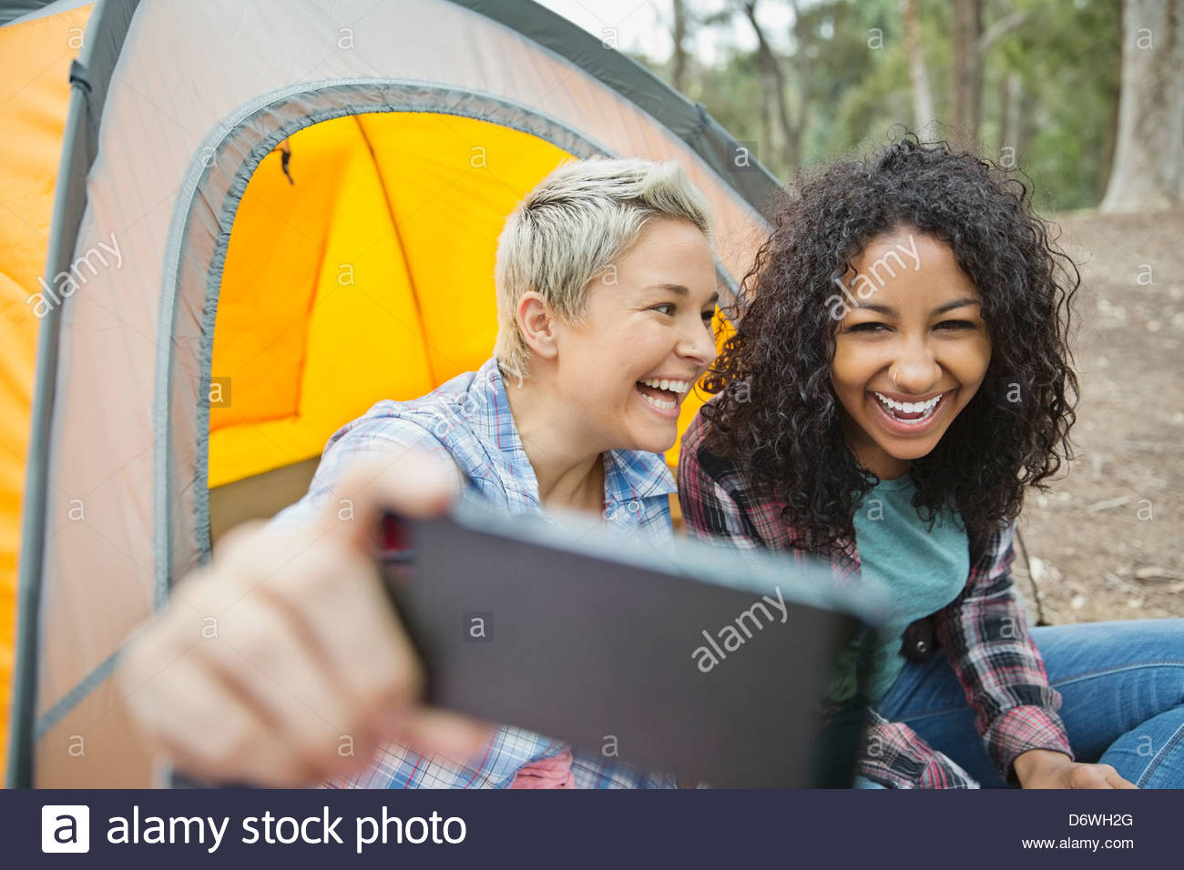 Female friends taking self portrait while camping - Stock Image