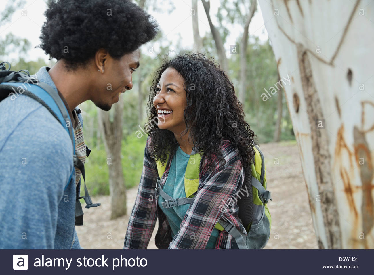 Happy romantic couple looking at each other in forest Stock Photo