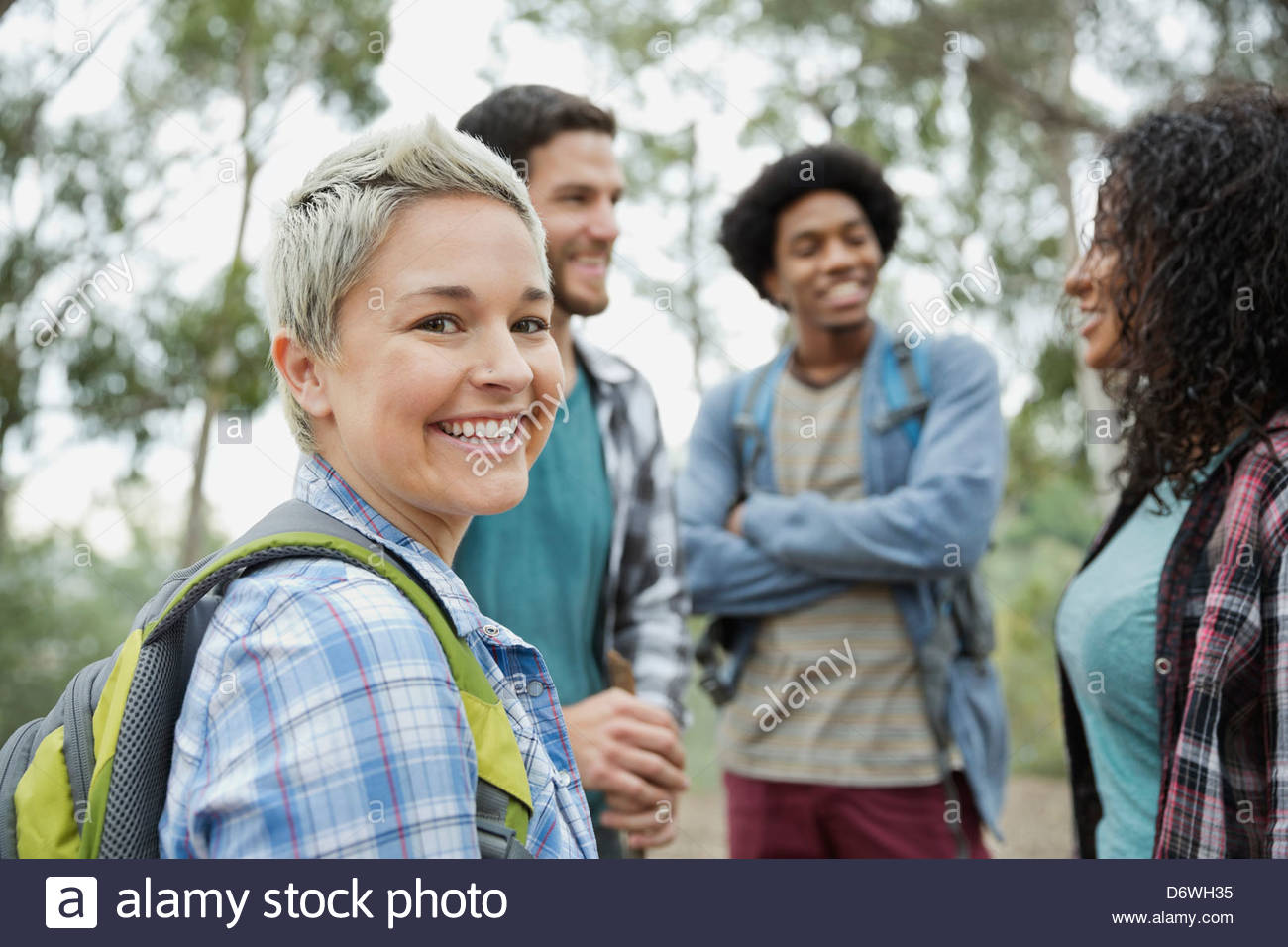 Portrait of happy mid adult woman with friends  in outdoors - Stock Image